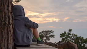 Cinemagraph - girl in a hoodie sits, and contemplates the sky. 4k, time lapse stock video