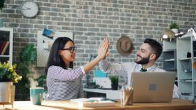 Cinemagraph of happy coworkers doing high-five in office at desk with laptop. Cinemagraph of happy coworkers doing high-five in office sitting at desk with stock footage