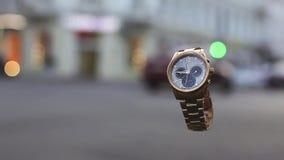 Cinemagraph Lijnvideo Leef foto Gouden horloges in de lucht en stadsverkeerslichten op achtergrond Kruispunt en de straat stock videobeelden