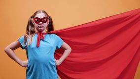CINEMAGRAPH - Little girl dressed in superhero with the cloak getting blowed by the wind. Over orange background. Power and superhero concept stock video footage
