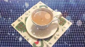 Cinemagraph - livlig snö som faller på den vita koppen kaffe med hjärta, formade kakan på en tabell med ett rutigt royaltyfri illustrationer