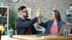 Cinemagraph loop of colleagues doing high-five sitting at table in office. Cinemagraph loop of happy colleagues man and woman doing high-five sitting at table in stock video