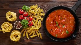 Cinemagraph loop. Cooking pasta penne with tomato sauce and basil on iron cast pan. Wooden table, top view. Cinemagraph loop. Cooking pasta penne with tomato stock video