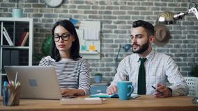 Cinemagraph loop of man moving pen in hand working in office with woman. Cinemagraph loop of man moving pen in hand working in office with young woman sitting at stock video