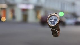 Cinemagraph. Loop video. Live photo. Golden watches in the air and city traffic lights on background. Crossroad and the street.  stock video footage