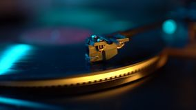 Cinemagraph loop vinyl record player turntable with it`s stylus running along music plate. Neon light. Retro-styled stock footage