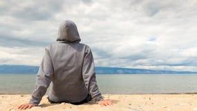 Cinemagraph - mannen eller kvinnan sitter i en hoodie på stranden tillbaka sikt 4K stock video