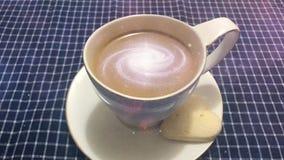 Cinemagraph - Melkweg in de kop van koffie Het stomen van witte kop van koffie met roterende melkweg daarin op een lijst met a stock video
