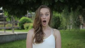 Cinemagraph of pretty cute young woman surprised shocked on green trees background. Loopable. Cinemagraph of pretty cute young woman surprised shocked on green stock footage
