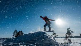 Cinemagraph Snowboarder del novato en un salto con un trampolín de la nieve ligera, paisaje del invierno, lazo video metrajes