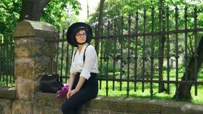 Cinemagraph - uma menina senta-se na cerca de pedra filme