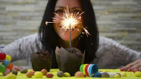 Cinemagraph van een vrouw die met een toorts op een muffin viert stock video