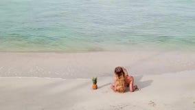 Cinemagraph van jonge vrouw ontspant op het strand stock footage