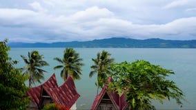 Cinemagraph von Toba See im wolkigen Wetter mit traditionellen batak Artdächern von Samosir-Insel, Nord-Sumatra stock video