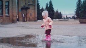 Cinemagraph: wenig Kind springt in eine Pfütze und verlässt viel Spray stock video