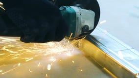 Cinemagraph zbliżenie iskry od kółkowego szlifierskiego maszynowego rozcięcia metalu profilu w warsztacie zdjęcie wideo