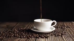 Cinemagrhe Xícara de café e feijão de café Xícara branca de café evaporante sobre a mesa com feijão torrado Movimento lento vídeos de arquivo
