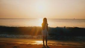 Cinematic achterdiemening van gelukkige meisje het letten op overzeese golf wordt geschoten die bij ongelooflijk gouden oceaanzon stock footage