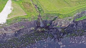 Cinematic aerial shot of the dramatic coastline at the cliffs close to the famous Kilt Rock waterfall ,Skye stock video footage