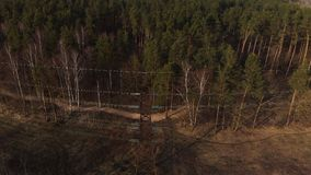 Cinematic aerial shot - Flying up the high voltage electricity tower and power lines at sunset above green forest in the stock video footage