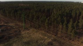 Cinematic aerial shot - flying up the high voltage electricity tower and power lines at sunset above green forest in the. City of Riga, Latvia stock footage