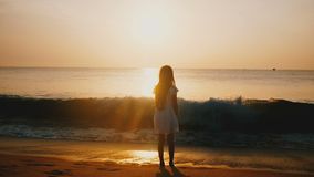 Cinematic back view shot of happy little girl watching sea wave coming on at incredible golden ocean sunset beach. stock footage