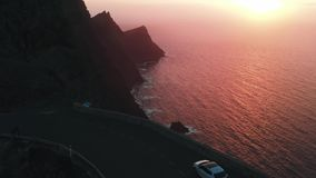 Cinematic beautiful shot with drone - a young man stands on a viewing platform on the edge of a high cliff above the. Atlantic Ocean at sunset. Mirador del stock video footage