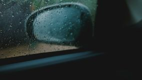 Cinematic close-up, defocused side view mirror is seen from inside the moving car, focus on rain drops on the window. stock video