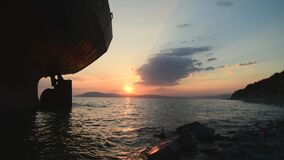 Cinematic footage of Cargo ship standing at shoal after run aground on sunset