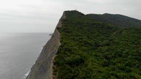 Cinematic luchtlengte van berg die vliegen De mening van Nice over berg met strand en oceaan stock videobeelden