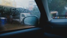 Cinematic middelgroot schot, mening op zijspiegel van binnenuit het autoraam die door Sri Lanka-stad onder zware regen drijven stock video