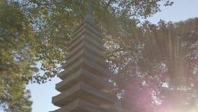 Cinematic panning of sunbeams over stone Japanese pagoda