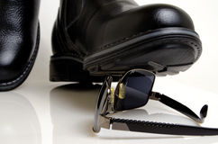Cinematic and photographic cliche. Shoe crushes sunglasses closeup on a light background Royalty Free Stock Image