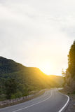 Cinematic road landscape. Asphalt Road throuth the mountains. With cloudy sky Stock Image
