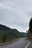 Cinematic road landscape. Asphalt Road throuth the mountains. With cloudy sky Royalty Free Stock Images