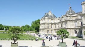 Cinematic scene elevated Luxembourg Palace Paris with waving flag. Paris, France - Circa 2017: Pan to Luxembourg Palace palais in the Jardin du Luxembourg with stock footage