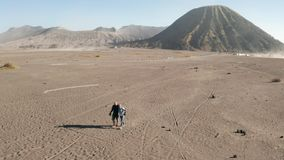 Cinematic shot aerial view of tourists walking in a volcanic dusty desert near beautiful Mount Bromo in East Java. Cinematic shot aerial drone view of tourists stock video footage