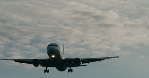 Cinematic shot of a passenger jet airplane about to land. 4K telephoto shot stock footage