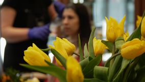 Cinematic view of a bouquet of yellow tulips in the beauty salon. The mirror reflects the woman who does hair coloring. Closeup stock video