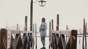 Cinematic wide shot of happy beautiful woman with camera enjoying perfect travel moments on romantic Venice gondola pier. Successful attractive tourist girl stock footage