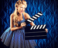 Cinematography. Pretty pin-up woman with retro hairstyle and make-up posing with clapper board over vintage background stock photography