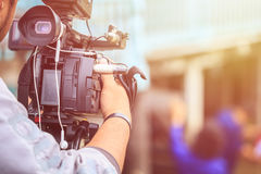 Cineoperatore che usando videocamera digitale professionale Impostazione esterna fotografia stock libera da diritti