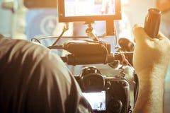 Cineoperatore con la sua fucilazione della videocamera fotografia stock