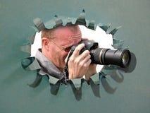 Cineoperatore della macchina fotografica che per mezzo della lente attraverso il foro nella travestimento dello strappo di innova immagini stock libere da diritti