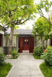 Cinese asiatico, costruzioni antiche, cortili, pistola bianca, mattonelle grige, porte e finestre rosse, alberi e fiori Fotografia Stock