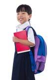 Cinese asiatico poca tenuta della ragazza della scuola primaria prenota con la borsa Immagine Stock