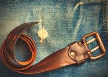 Cinghia d'annata sulle vecchie blue jeans Fotografie Stock Libere da Diritti