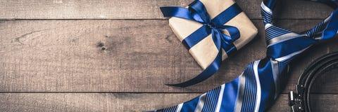 Cinghia del legame e contenitore di regalo sulla Tabella di legno fotografia stock libera da diritti