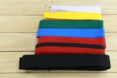 Cinghia di colore di varietà di arte marziale sul pavimento di legno Fotografia Stock
