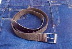 Cinghia elastica di allungamento di Brown sull'blue jeans Fotografia Stock